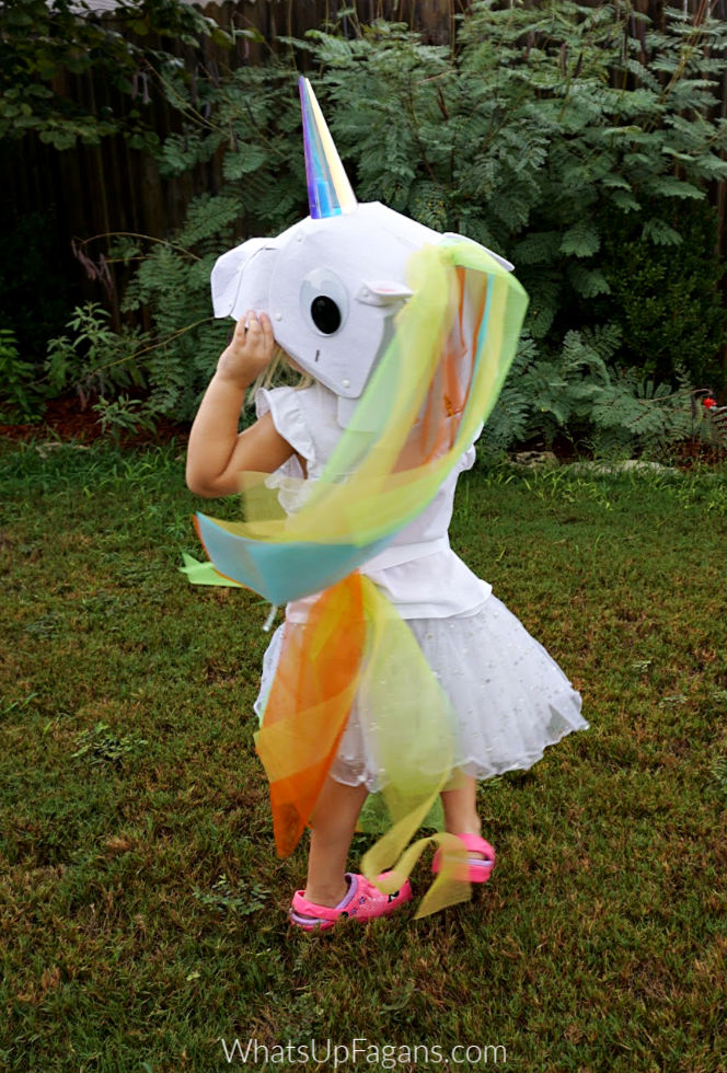 little girl in unicorn costume DIY in green backyard
