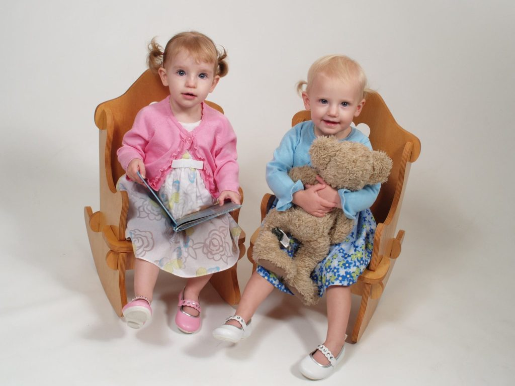 Picture of twin girls sitting in rocking chairs and holding a book and teddy bear. Tips on how to get good family photos.