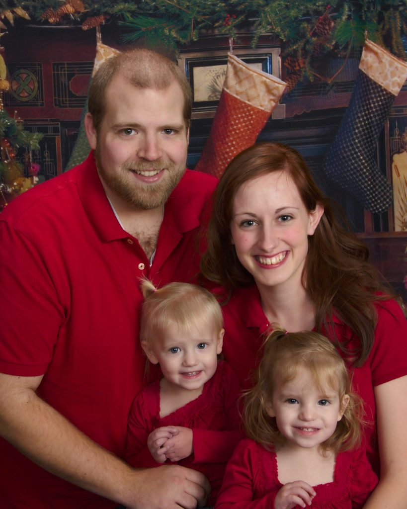 Mom and dad and twin daughters smiling for a family Christmas photo. Tips for family pictures.