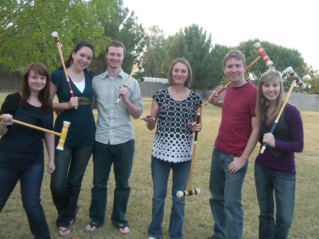 a group of adult friend playing backyard games like croquet which can also be fun for kids.