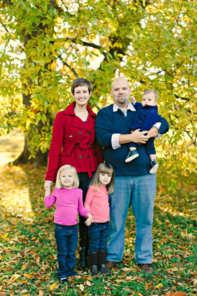 Family Christmas Photo of Mom, Dad holding baby, and twin daughters. What to do in order to prepare for family photos.