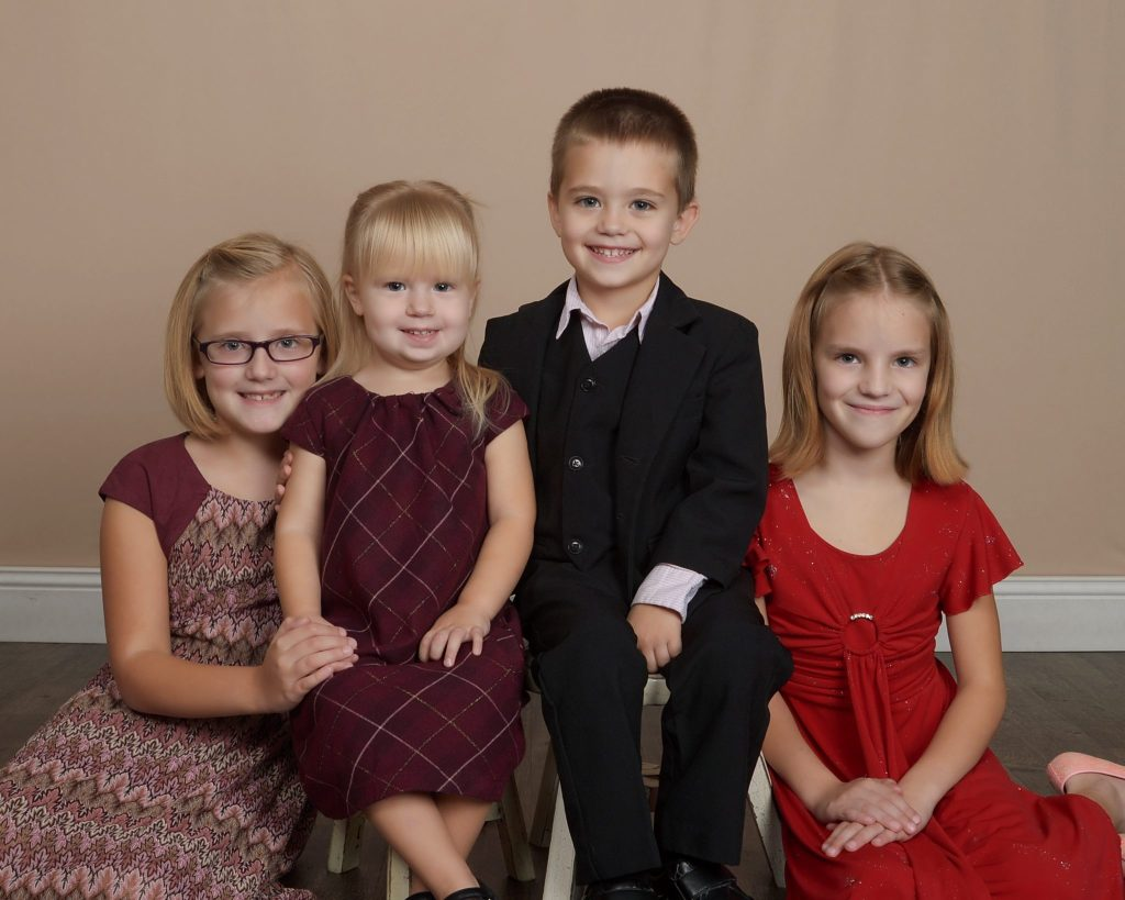 Four young children, three girls, with the one boy in the middle. What to wear for family photo tips - color and dress coordinate.
