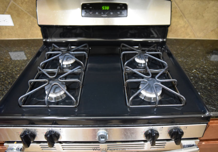beautifully clean gas stove top with clean gas stove burners and clean gas stove grates and clean gas stove burners. It's a black enamel gas stove top