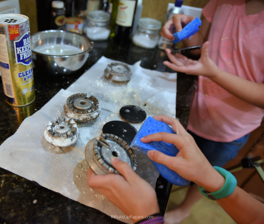 two young girls cleaning gas stove top burners and burner heads with scrubbing blue sponges