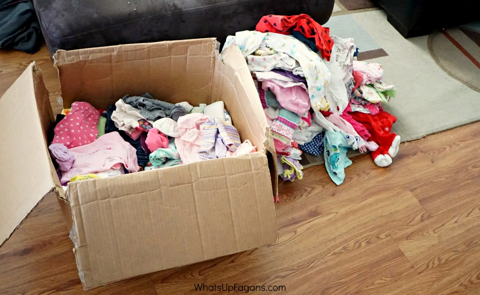 box of baby clothes next to a pile of baby clothes storage