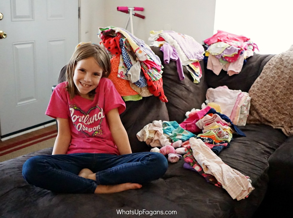 young girl sitting on a couch working on storing baby clothes as she sits next to piles of organized and sorted baby clothing