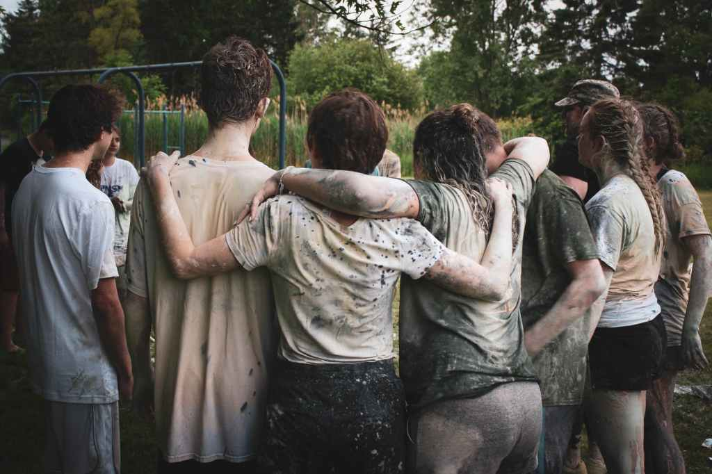 group of hugging, muddy teenage children, showing that the more parental invovlement the more you improve your child's social skills