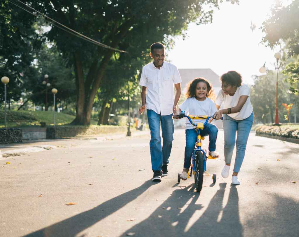 parents helping daughter bike in the street, showing an example of parental involvement