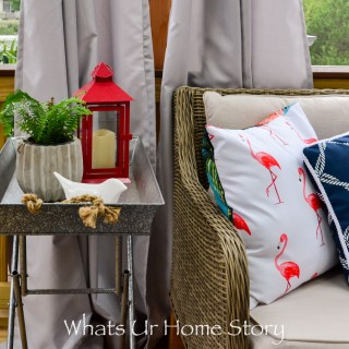 Love this outdoor space with a beautiful red and blue outdoor decor with a flamingo pillow, metal tray side table, and loads of green plants