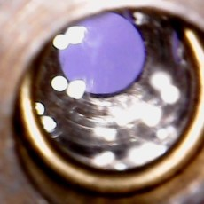 Close up of lens in objective. White spots of light reflecting on the glass.
