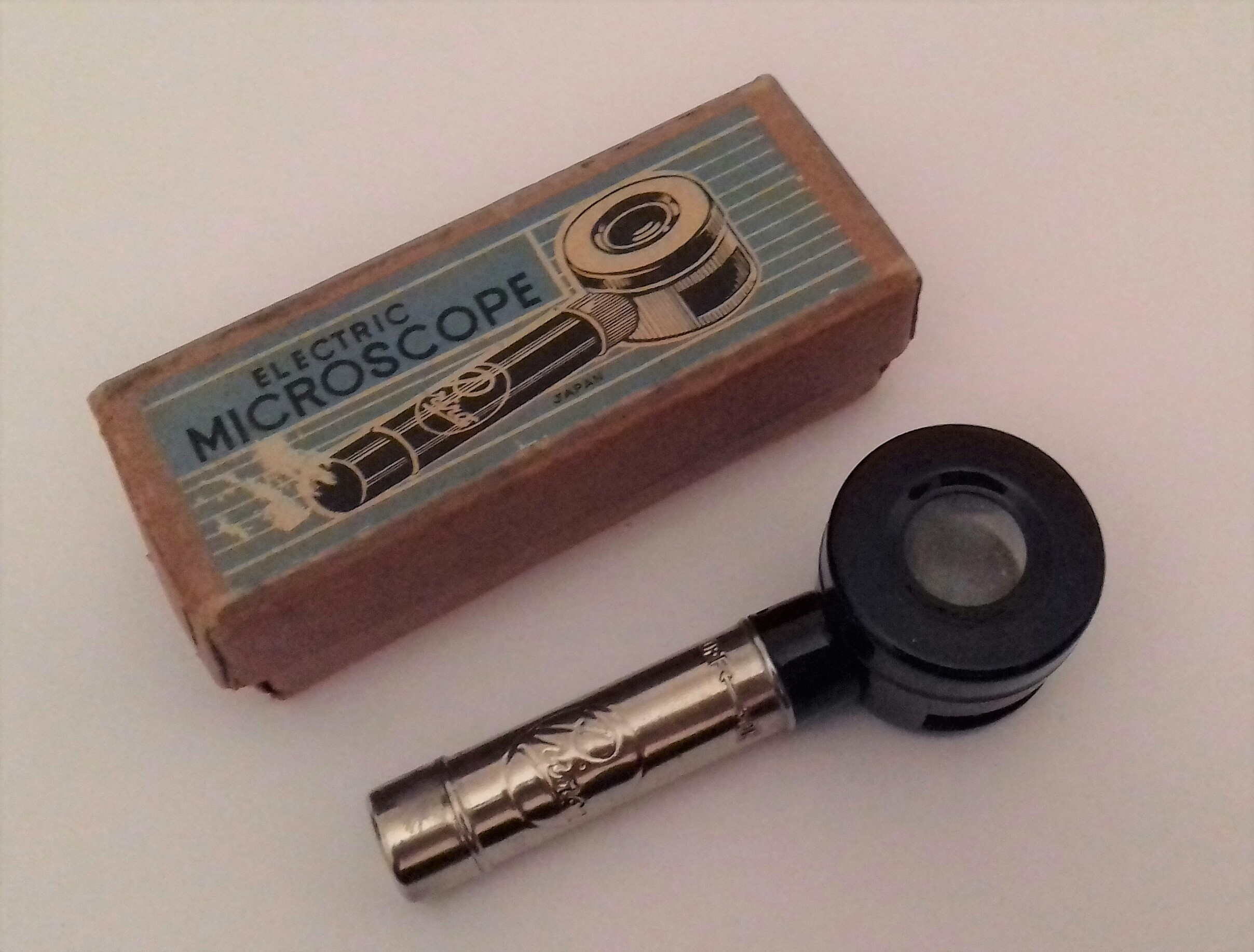 A toy microscope that is a small round lens on a handle