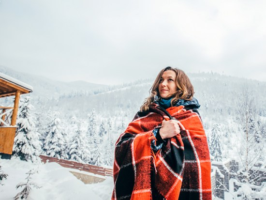Woman Wearing Afghan Outisde Snowy Cabin