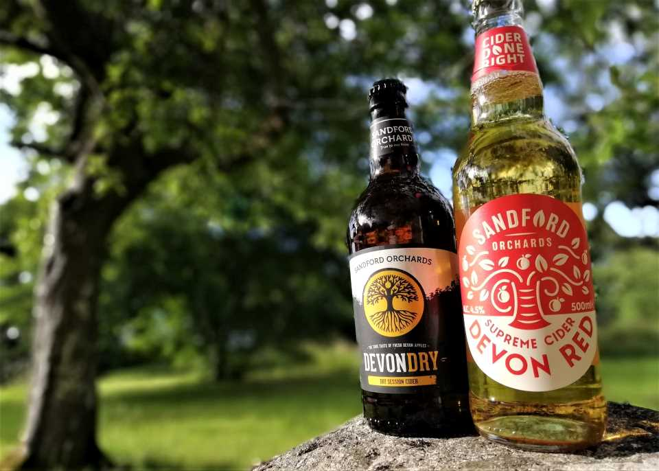 Shows 2 bottles of cider in an orchard at Wheatland Farm
