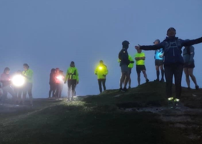 Runners seeing in the solstice dawn atop Little Hound Tor, Dartmoor