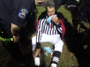 Peter McCabe, a referee of a football game in Rochester, N.Y., is tended to after being allegedly struck in the face by a player swinging a helmet.