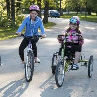 4 girls riding bikes, one of which is an adaptive bike by Freedom Concepts