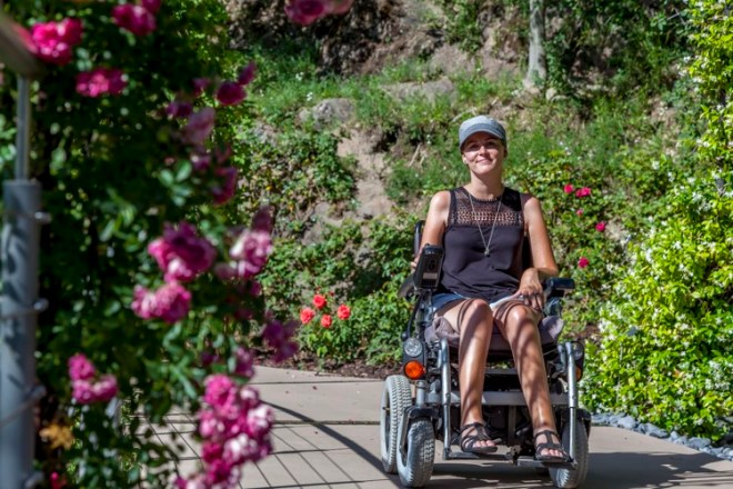 Bibi in her wheelchair on a cement path with greenery and flowers surrounding her.