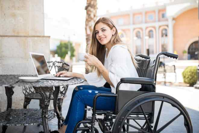 young woman in a wheelchair drinking coffee in a cafe and working on her computer