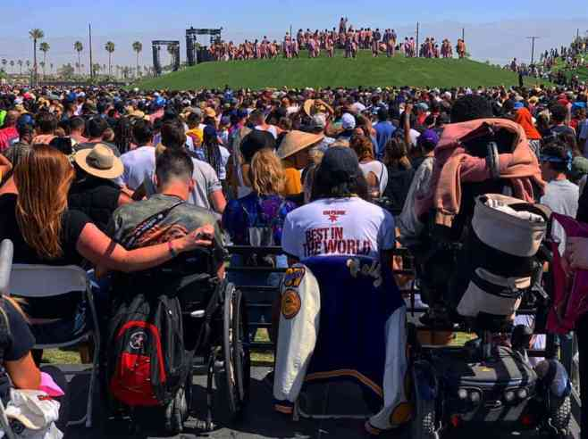 crowd of people from behind at an outdoor festival with two wheelchair users. A grassy hill with people on it is in the distance.