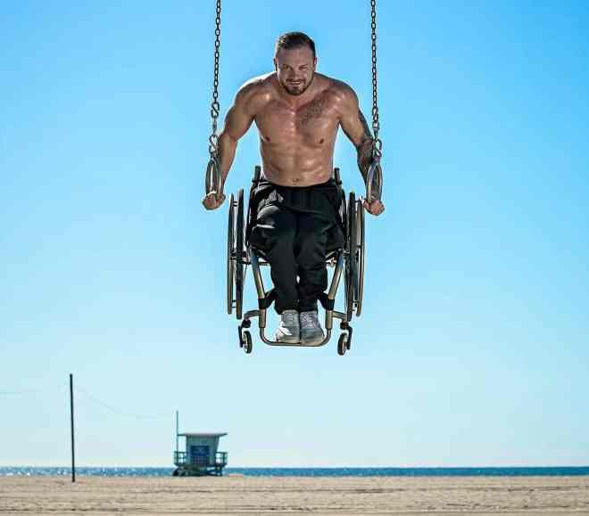 Richard Corbett is shirtless with black pants sitting in his wheelchair while doing a gymnastics ring hold at a beach