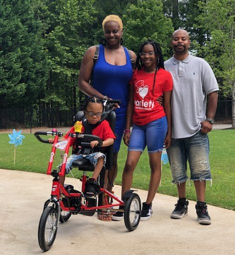 A young girl with her red Freedom Concepts adaptive bike. Her parents and sister are standing behind her.
