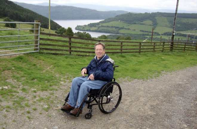 Jim Parsons is sitting in his wheelchair in a blue jacket. In the background, we see grassy hills and a winding river.