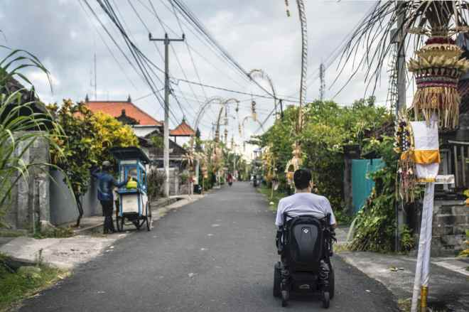 Minna riding down a street in Bali in his wheelchair