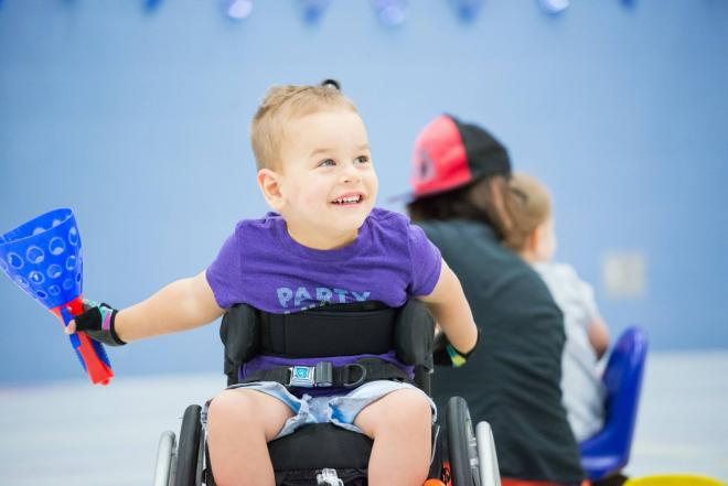Noah, a little boy, is in his wheelchair in a gym. His has a big smile on his face, and we see some other people in the background.