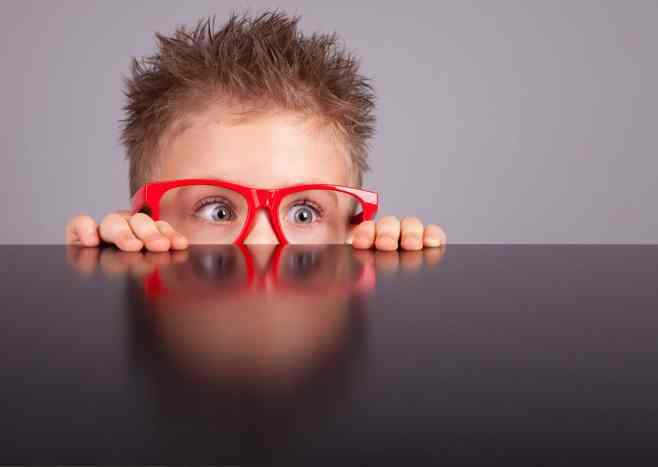 Little boy with red glasses peering out from behind a table.