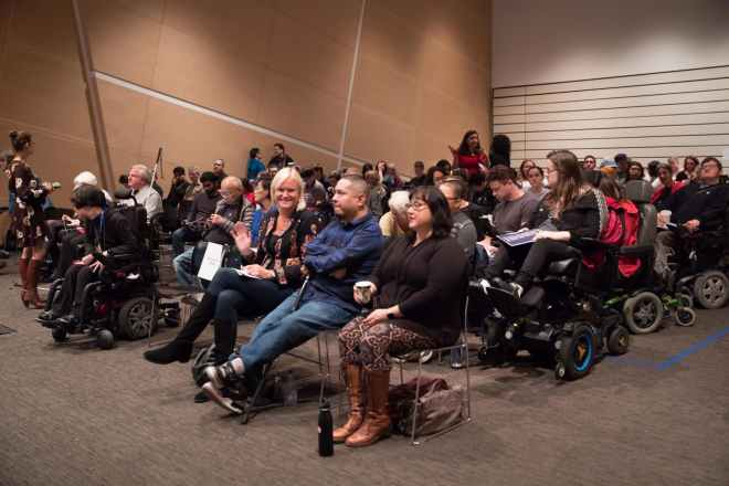 A group of people, some in wheelchairs, sitting in a room for a Superfest screening.