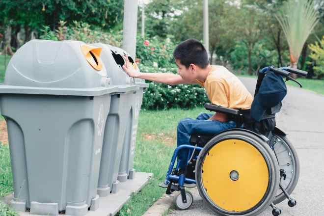 Young boy in wheelchair with yellow wheels reaches from his chair to put an item in one of three recycling or trash bins.
