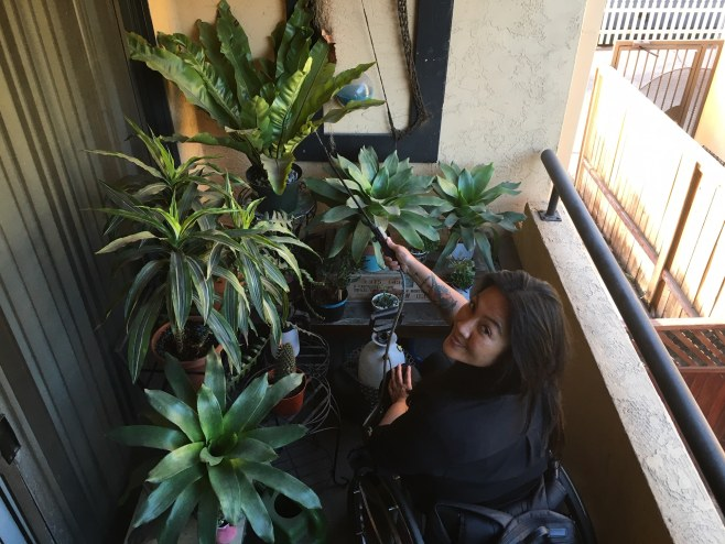 Hydred Makabali, a woman in a wheelchair, looks up at the camera from her balcony filled with house plants.
