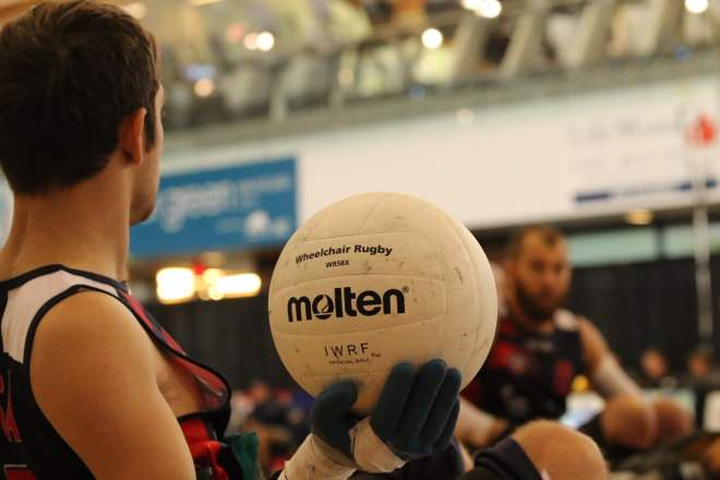 "A profile view of Butler from the chest up holding a Molten volleyball that says, ""Wheelchair Rugby"" and ""IWRF Official Ball."""