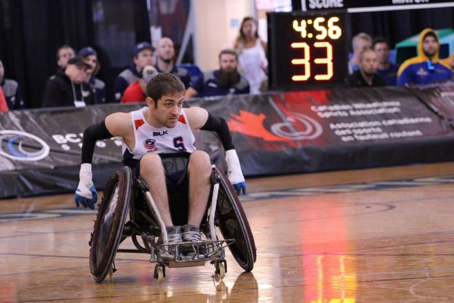 Jeff Butler in a wheelchair made for wheelchair rugby on the court. The scoreboard is partially visible as well as spectators in the background.