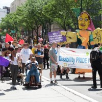 A group of people march and roll at Disability Pride Philadelphia parade.