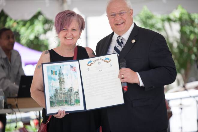 Vicki Landers and a man hold up resolution document.