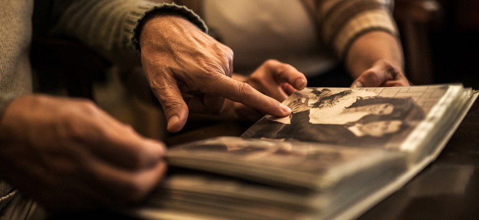 Unrecognizable seniors remembering their old times by looking at photo album.