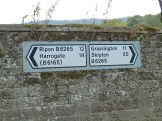 Signs on a wall in Pateley Bridge, on the undulating B6265.