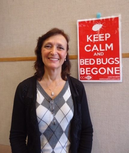 Dr. Gale Ridge with sign about bed bugs