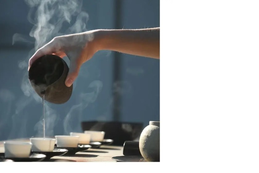 "Steaming hot Chinese tea is poured from the ""fairness jug"" 