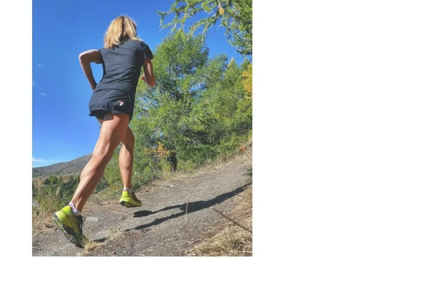 Woman in sports gear training up hill