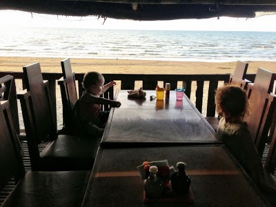 sitting at a restaurant table at seafood shacks with baybay beach in the background, roxas city with kids