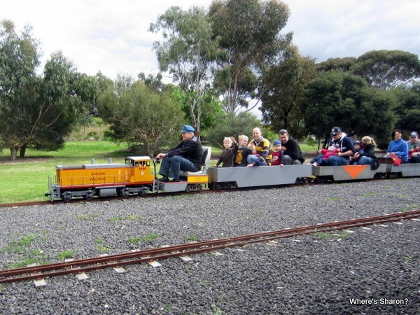 people riding miniature train