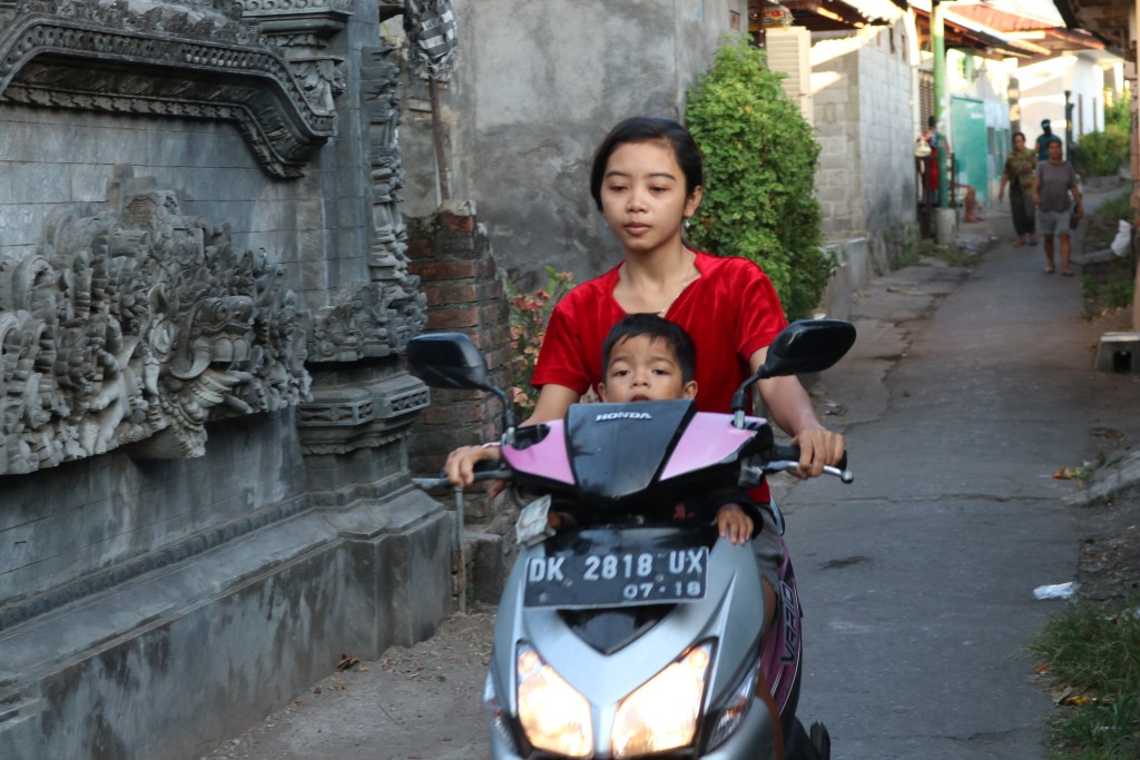 Young girl and baby on a motorbike.