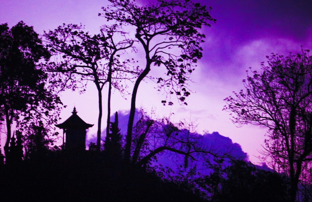 Balinese temple silhouetted at sunset.