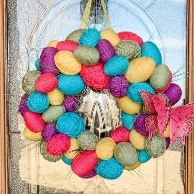Yarn-wrapped Easter egg wreath hanging on glass door.