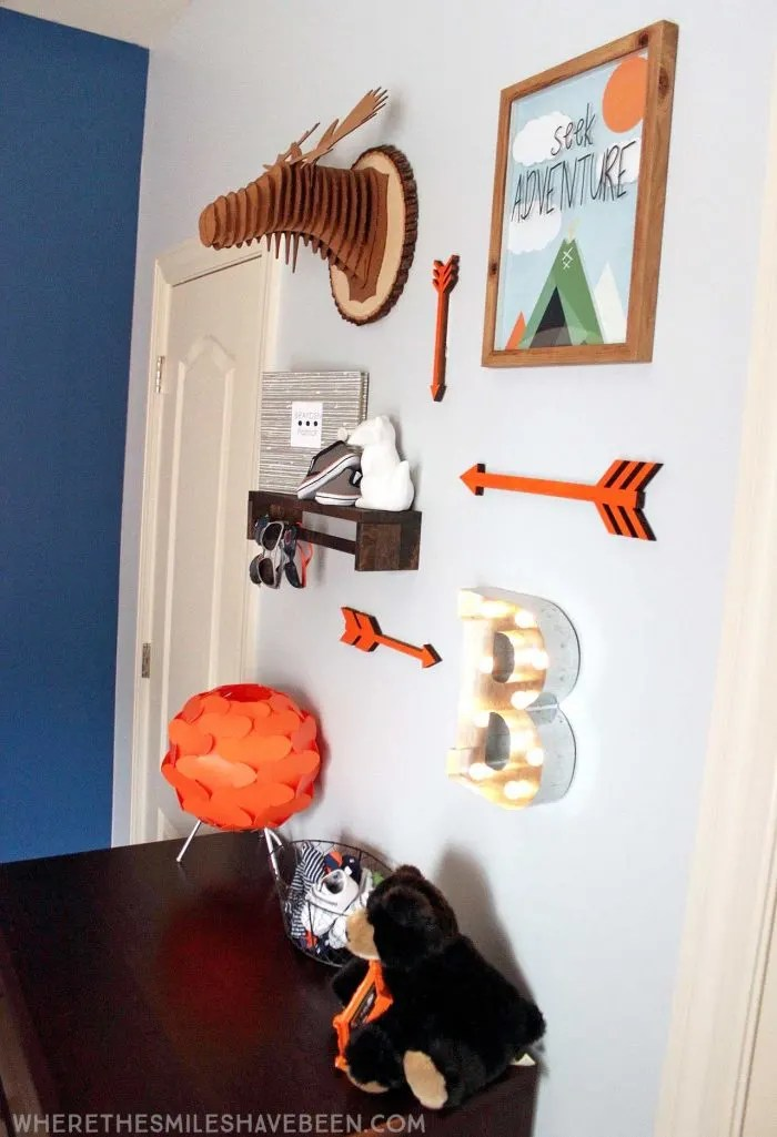 LOVE this mini gallery wall in a baby's room! That moose head and shelf are great! Take a tour of this navy & orange modern woodland nursery! | Where The Smiles Have Been