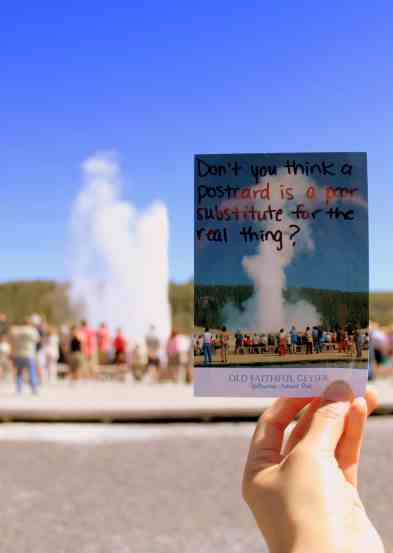A picture of me holding up a postcard with Old Faithful on it, in front of Old Faithful erupting.