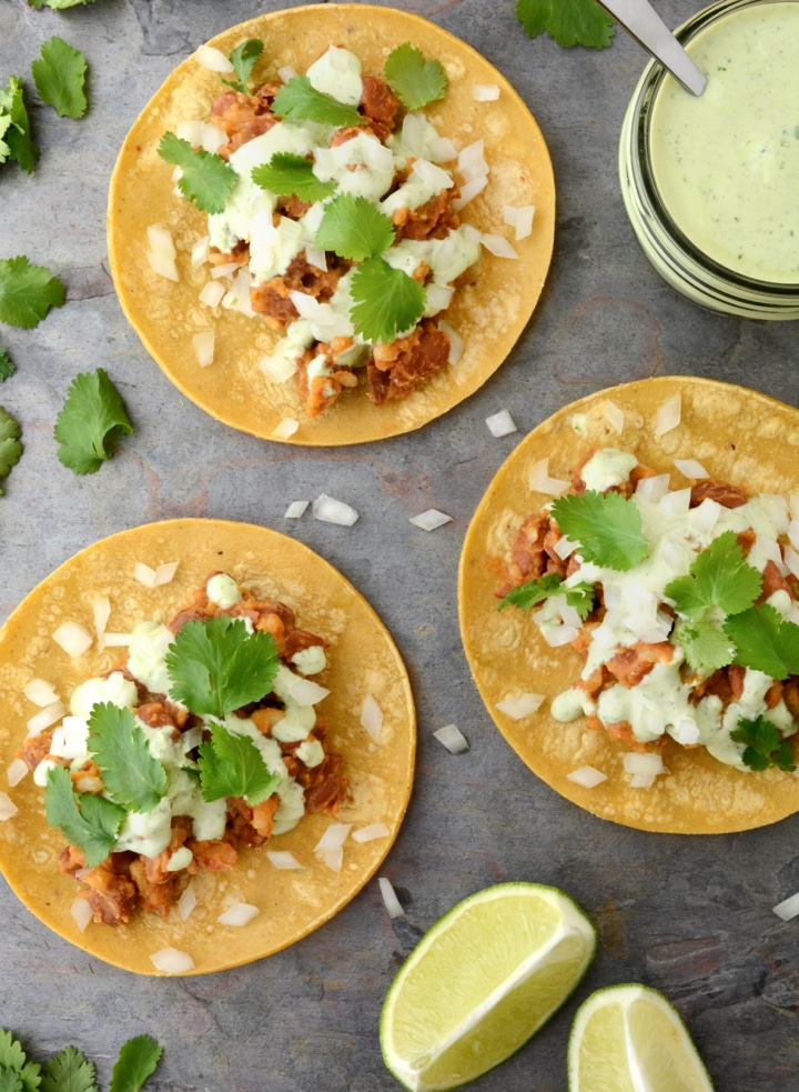 Vegan Tacos with Cilantro Lime Sauce are gluten-free and oil-free. These healthy 20 minute tacos are so easy to make and only take one pan! The filling is made with seasoned pinto beans and rice. Then the tacos are topped with a tangy cilantro lime sauce.