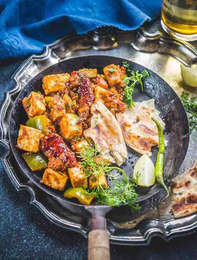 Kadai Paneer served in a plate along with lachha paratha